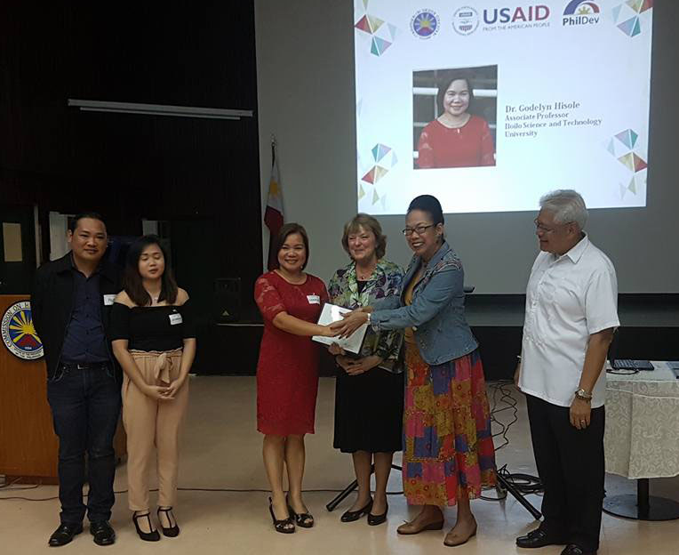 Dr. Hisole recieves the award with Dr. Russ Allen B. Napud (far left) Dean, College of Engineering and Architecture.