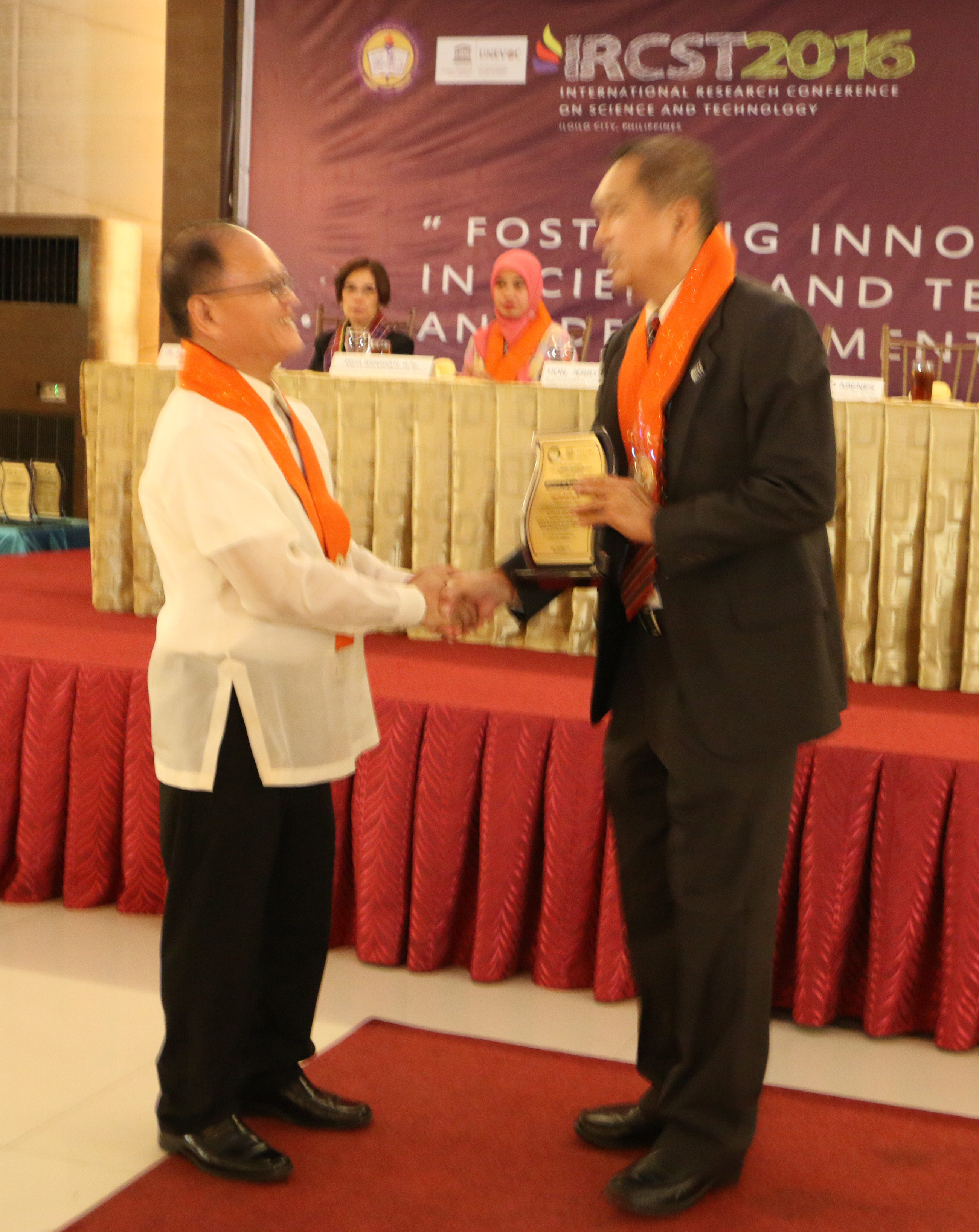 ISAT U President Dr. Raul F. Muyong gives the Plague of Recognition to Dr. Fiorillo B. Abenes of the USAID-STRIDE.