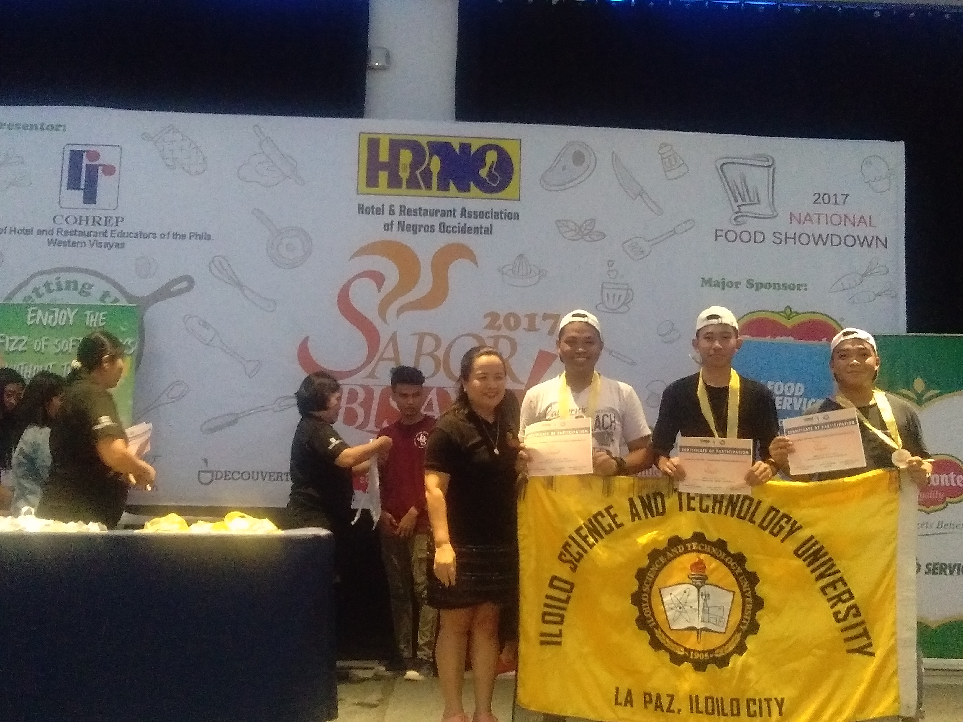 Kenneth Gregg Bargo, Aldrin Cancillar and Christian Pacino proudly holds the ISAT U banner as they receive the certifificate of regognition as the champion of the culinary competition.