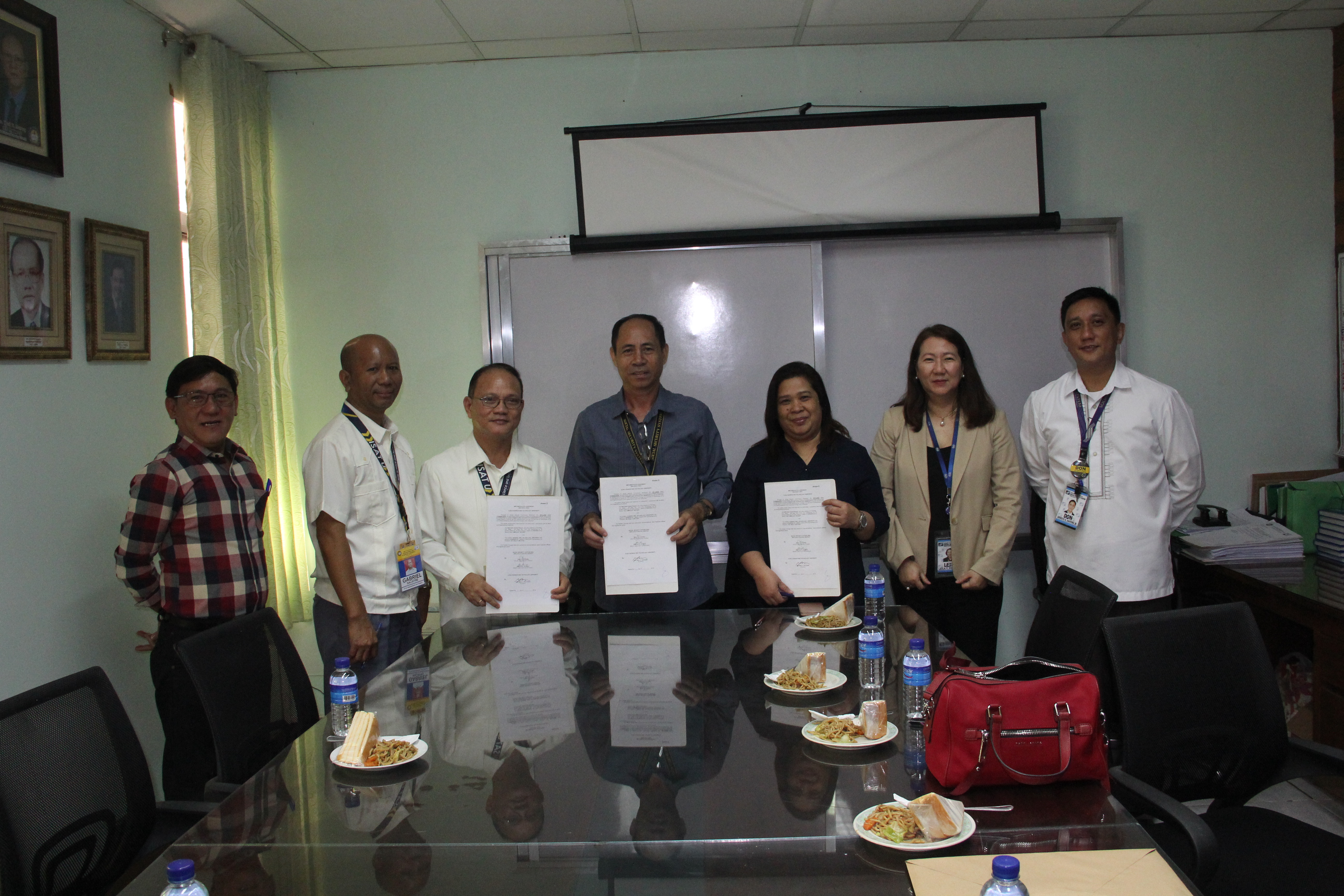 Dr. Raul F. Muyong and Mr. Raul A. Casiano, Branch Manager, SSS Western Visayas, sign the Implementation Agreement for the PASUC-SSS Memorandum of Agreement for the registration and voluntary membership of Job Order and Contract of Service Personnel on January 22,2018 at the ISAT U President's Office Conference Room. Also in photo are Mr. Bonnie S. Arenal, ISAT U HRMO; Dr. Gabriel M. Salistre, Jr., VPAF and Ms. Emelia Solinap, Leila Ferraris and Mr. Ernesto D. Juayong, Jr. of the SSS.