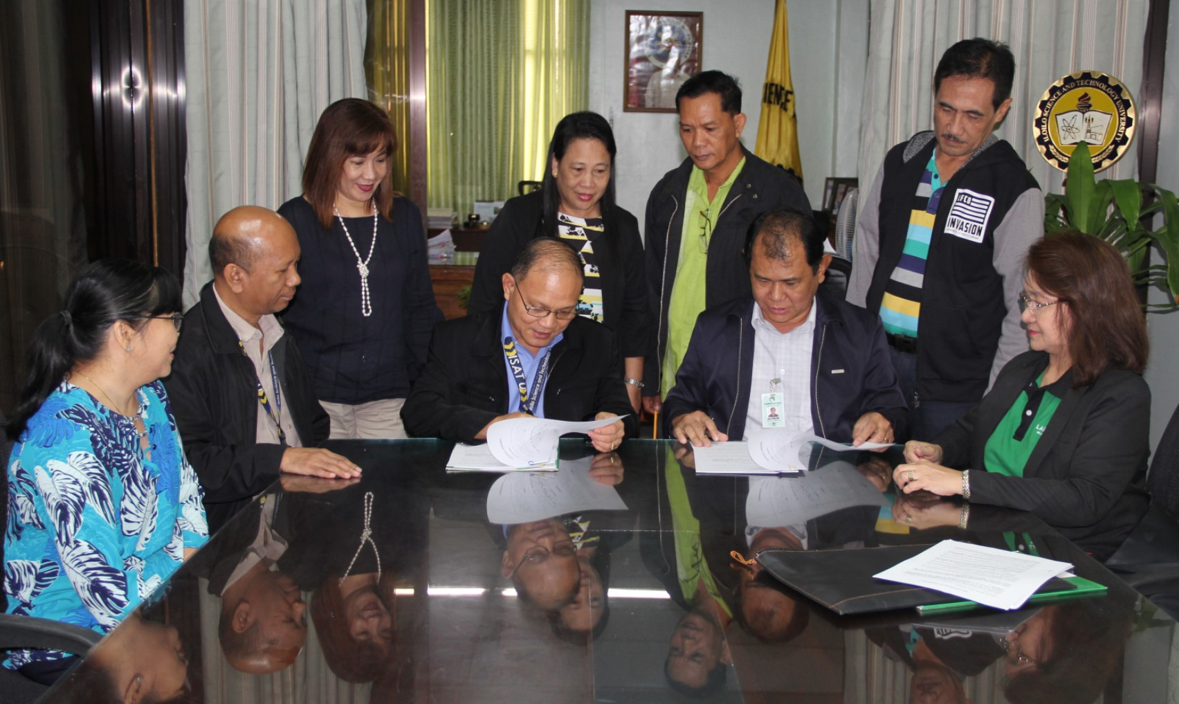 Dr. Raul F. Muyong and Mr. Althon C. Ferolino, Head, LBP West Visayas Branch Group, sign the Memorandum of Agreement for a 25 year usufruct of the 600 square meter lot for Land Bank Branch at ISAT U Miagao Campus. Land Bank of the Philippines will give a Php 5 million goodwill for the construction of a mini grandstand at the school ground. The ceremony is witnessed by (l-r) Dr. Sandra T. Examen, Miagao Campus Administrator; Dr. Gabriel M. Salistre, Jr., VPAF; Maria Luisa N. Eiman, Chief Administrative Officer, Miagao Campus; Dr. Herminia Falsario, Mr. Ely Ciasico, Mr. Arcenio Montano, Jr. and Ms. Rowena H. Areno, Branch Manager, LBP Miagao Branch.